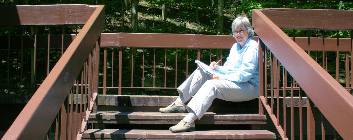 Terry Modica writing on the steps outdoors at Pipestem Lodge