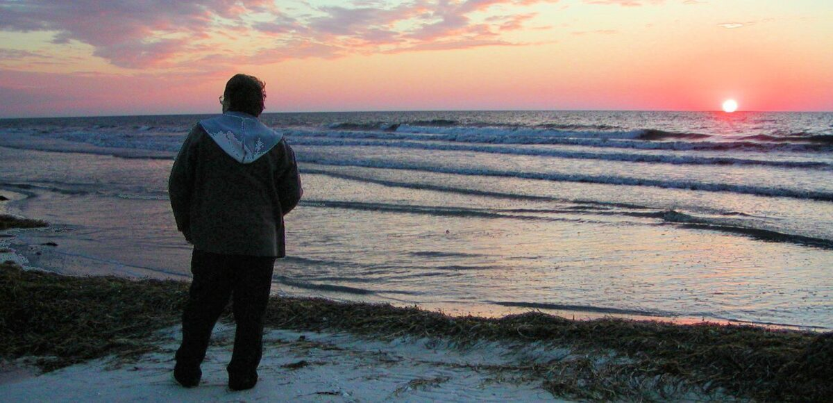 man alone on beach at sunset